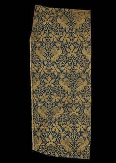 This woven silk is one of the most expensive luxury textiles of the 14th century and might have been used for secular or ecclesiastical dress or furnishings.    The exotic birds and vine leaves in its composition represent designs that were new at the beginning of the 14th century. Birds and plants flow freely across the textiles, the former depicted in active poses, often ranged in pairs facing each other. Vine leaves also feature prominently.