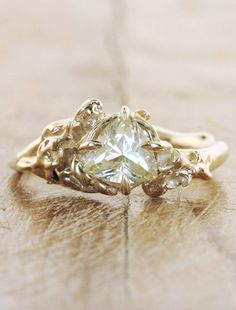 The Elsie features a 0.84 ct fancy-cut natural yellow sapphire.  This rare center stone is set in a 14k yellow  gold setting with organic fl...