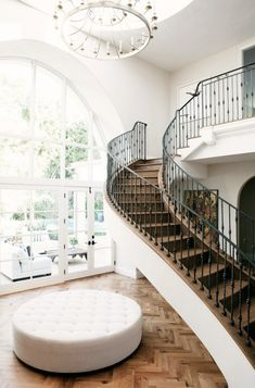 Sweeping staircase with a wrought iron banister and parquet wood flooring.