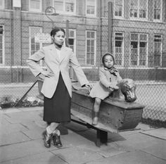 East London Afro-Caribbean child and mother in playground, 1952. The years between 1948 and 1962 saw the migration to Britain of several thousand Caribbean people. They were attracted by jobs in the health service, transport and catering industries. Most of them were men who were not joined by their wives and families until they had established themselves. So a Caribbean mother and child in London would have been a relatively unusual sight at this date.(Henry Grant Collection, Museum of…