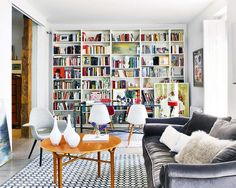 Alternative view a living room in an apartment with built in bookshelves, a grey sofa, grey armchair, wood table, a blue and white graphic p...