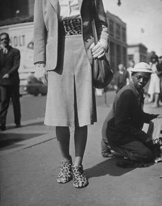 Matching Shoes  Young African American shoeshine youngster expressively responding to model walking by wearing matching leopard cumberbund and shoes,  Location:	New York, NY, US  Date taken:	August 1946  Photographer:	Nina Leen