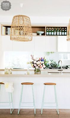 Mint green stools are a sweet touch in this light and airy kitchen.