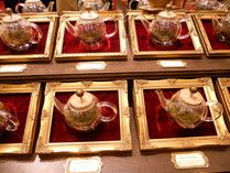 Loose tea is showcased in glass teapots in gilt frames at the Fortnum & Mason Tea Room, London