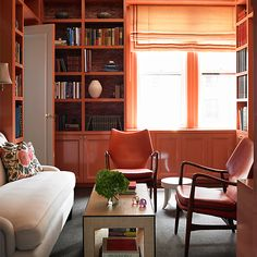 Glossy coral walls look très chic, especially in small spaces like a study, an office, or a powder room.