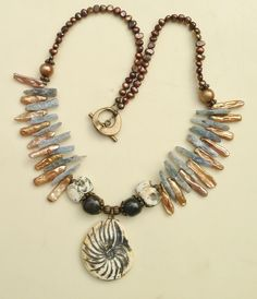 by Sheri Mallery Using my porcelain shell pendant and beads,  kyanite, and freshwater pearls.