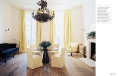 Slipcovered chairs and a cream, ivory, butter, navy, walnut wood palette dining room.