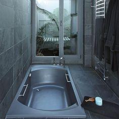Razionalizzando gli spazi si guadagnano centimetri e aumentano le possibilità compositive: il bagno ritratto in questa foto ha, infatti, tutte le caratteristiche di una piccola spa. La vasca, a filo pavimento, è essenziale ma capiente (e cromaticamente coordinata con i rivestimenti di pareti e pavimento), la stanza sul fondo accoglie una sauna per due e il porta asciugamani è, allo stesso tempo, un radiatore.