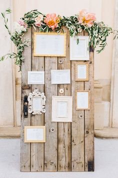 Filled with seating charts, mismatched frames were hung on an old detached door draped in flowers and foliage. | Photo by  Tony Gigov