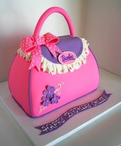 Pink and purple fondant covered Barbie purse cake with fondant bow