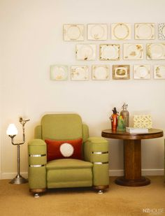 """Art Deco in Taranaki - In the family room, a 1930s armchair sits between an art deco """"smoker's companion"""" and an oak deco side table displaying the green chintz plate that sparked Jane's Biarritz plate collection, also seen on the wall behind."""