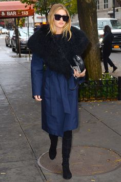 Gigi Hadid steps out in a navy coat with a fur collar and black boots. See all her best style and outfits here  - HarpersBAZAAR.com