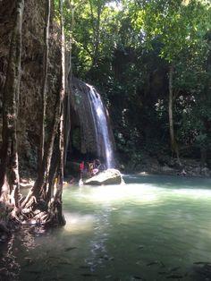 People playing in the waterfalls at Erawan Falls, Thailand