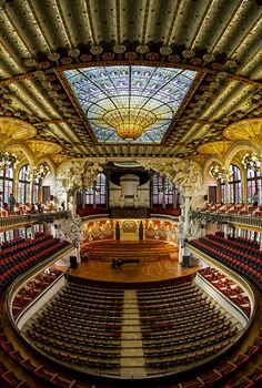 "The Palace of Catalan Music - located on a crowded street in Barcelona, Spain. This concert hall was inaugurated in 1908 and declared a World Heritage Site in '97. The hall seats 2,200 people,  and is the only auditorium in Europe that is illuminated entirely by natural daytime light. This is due to skylights and intricate stain-glassed designs. More than half a million people a year attend musical performances in what is said to be ""the most beautiful concert hall in the world"". We agree!"