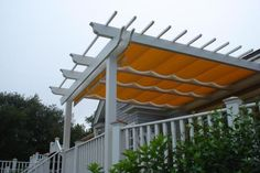 easy way to add a retractable cover to a pergola: attach a curtain rod on top of each side and put shower rings on your cloth cover