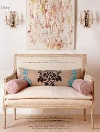 A warm feminine feeling surrounds this space with the large art work flanked by 2 wall sconces, antique settee with a patterned lumbar pillow....a lighter shade of pink.