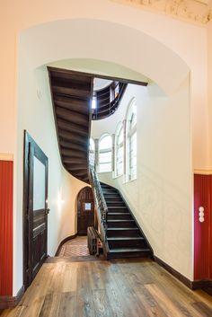 Über diese schwungvolle Holztreppe gelangt der Besucher vom Foyer ins obere Stockwerk. Im Hintergrund links erkennt man die Original-Jugendstil-Bodenfliesen.
