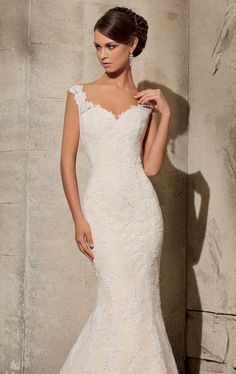 Be swept away in timeless romance in Blu by Mori Lee 5316. This exquisite wedding gown features a v-neckline with thick straps. The rich Alencon lace accentuates the net fabric, that wraps the bodice over sweetheart lining. The heart inspired sheer back is created with covered buttons, paneling the center for added flair. The fit-and-flare skirt shapes the perfect slim silhouette, complimenting your gorgeous look. Removable tulle overskirt not included.