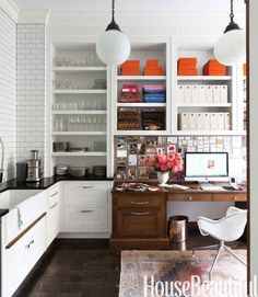 In designer Nina Farmer's Boston brownstone, the kitchen pantry also houses her office. To the right of the Waterworks Fireclay Farmhouse sink, open shelves hold plates from Hermès and Match, above cabinets with polished nickel Bistro pulls from Restoration Hardware. Urban Archaeology's Savoy globe fixtures illuminate the built-in desk, B & B Italia chair and antique Oushak rug.