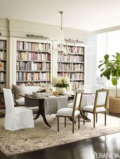 A cream, gray and taupe Oushak rug contrasts with a dark brownish-black lacquered floor and complements white walls and dark wood tones in the dining room of the Houston penthouse of a fashion designer.