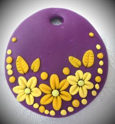 Polymer clay pendant, handmade with applique technique, one of a kind. Purple with flowers, leaves and dots in various shades of yellow. By Lis Shteindel.