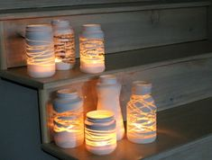 + Ideas for Beautiful and Ingenious Mason Jar Crafts mason-jar-decorations-seven-jars-of-different-shapes-and-sizes-decorated-with-white-paint-containing-lit-candles-placed-on-wooden-steps Pot Mason, Mason Jar Crafts, Mason Jar Diy, Diy And Crafts Sewing, Crafts To Sell, Fun Crafts, Candle Lanterns, Diy Candles, Craft Wedding