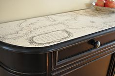 """LOVE this DIY """"found cabinet"""" top.  I've always had a thing for maps, and this is something that MUST be in my house.  Maybe transforming the top of my Target wood desk to use in the library with the map I made for our wedding cake?  Hmmmm...  --Meggie"""
