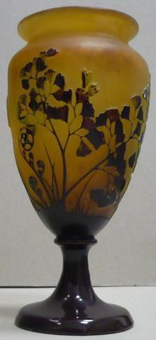 Emile GALLE (1846-1904), vase en verre multicouche marron foncé et vert sur fond ocre, de forme fuselée, à lèvre évasée, reposant sur un piédouche, il présente un décor dégagé à l'acide de motifs floraux, notamment de fougères. Signé : « Gallé ». Hauteur : 20 cm.