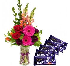 A mix flowers arranged in a vase with Cadbury Dairy Milk chocolates.