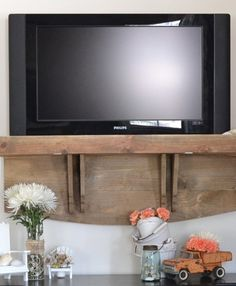 brilliant idea! Her TV was mounted on the wall ..she tucked a shelf underneath with a secret compartment to hide the DVR box!