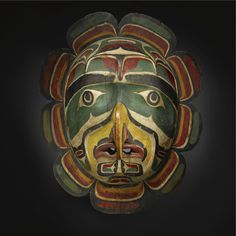 LARGE KWAKIUTL POLYCHROMED WOOD SUN MASK. Carved with a totemic hawk's face, with broad downward turned mouth, large hooked nose with slightly rounded nostrils, ovoid eye rims and thick arching brows, painted overall in black, white, gray, red and deep green with curvilinear decorations; elaborate scalloped border carved separately and attached along the back.