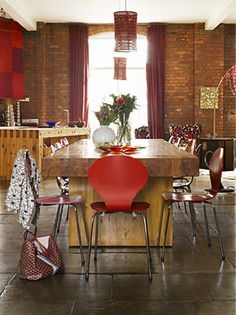 Exposed brick and tall window with red curtains.