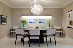 O jogo de preto e branco domina a sala de jantar do apartamento em Guarulhos (SP), com interiores da arquiteta Marília Brunetti de Campos Veiga. O ambiente tem mesa oval e cadeiras da Empório Vermeil em harmonia com o bufê executado por Takae Arte. Na parede cor de fumaça, iluminando o bufê, destaque para a enorme arandela horizontal da Lumini que também assina a luminária pendente sobre a mesa. Tela de Flávia Brunetti