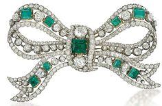 And Antique Emerald and Diamond Bow Brooch. The articulated ribbon bow mounted with graduated old-cut diamond collets alternated by square-shaped emeralds to the diamond line borders and three-stone centre, mounted in silver and gold, circa 1880, 12.0cm wide, in original purple velvet fitted case by Garrard & Co.