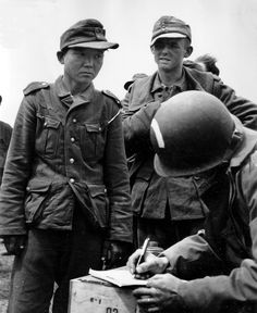 Yang Kyoungjong, an ethnic Korean soldier in the German Wehrmacht, captured by US Army soldiers in France after D-Day in June 1944