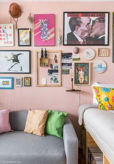 Parede de quadros pintada de rosa e sofá cinza pequeno