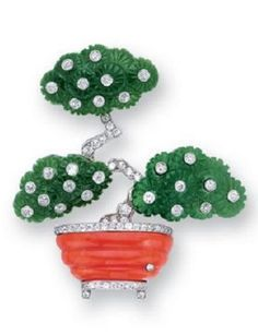 A Nephrite, Coral and Diamond Brooch, circa 1930. The giardinetto designed as a blooming bonsai tree of carved nephrite flowers with diamond collet centres, from the diamond stem to the carved coral jardiniere with diamond pedestal and trim, mounted in platinum.