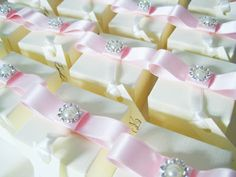 Pretty in pink wedding favour boxes with pearls. Dior style bow in light pink with small diamante and pearl brooch. Each favour box is personalised with wedding guests name