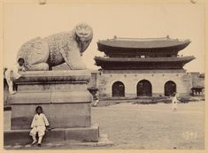 Kids posing next to the 'Haetae' statue, a mythical guardian beast, in front of the Gwanghwamun Gate, an area that will be the future downtown Seoul, Korea, 1890s-1900s