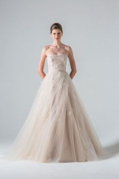 A modern bride wearing a strapless princess wedding dress with blush hues and embellished flower details within the tulle skirt.