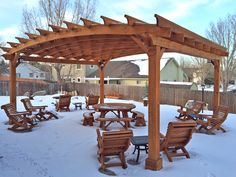 Arched Pergola (Options: 20' L x 24' Arc W,  Mature Redwood, Unattached, 4 Electrical Wiring Trims, Arched Roof with Lattice Panels, 4 Post Anchor Kit for High Wind, No Ceiling Fan Base, No Privacy Panels, No Curtain Rods, 10' Post Height, Transparent Premium Sealant). Extra Thick Lumber. Photo Also Shows a Round Picnic Table Set, 4 Ensenada Easychairs, 4 Ensenada Rocking Chairs, and a Lutyens Bench in Background. Photo Courtesy of Mike Budzinak in of Cheyenne, Wyoming.