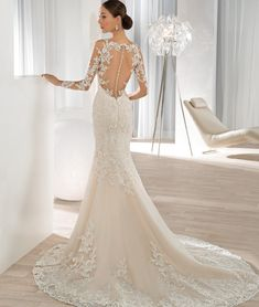This shimmering beaded lace fit n flare gown features a scoop illusion neckline with sheer long sleeves and lace appliques, that transition to the sheer dramatic back. The back is embellished with button closures and a Chapel train.