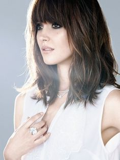 Rose Byrne wears vintage bangs. They are full, cover the entire forehead, and are layered downward at an angle meeting the sides of hair. Good for adding dimension and the appearance of volume to your tresses.
