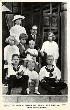 Queen Victoria Eugenie (standing, white hat) with her husband King Alfonso XIII, her mother-in-law Dowager Queen Maria Christina (sitting, holding Infante Gonzalo), and her children. Children Standing: Infanta Maria Christina, Infante Gonzalo (held) and Infanta Beatriz of Spain. Children Sitting: Infante Jaime and Infante Juan of Spain, and Alfonso, Prince of Asturias