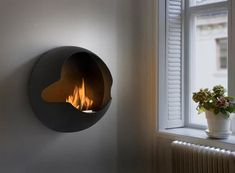 """""""The Versatile Globe Fireplace by Vauni Here is a cool, modern, and very versatile ventless ethanol fireplace from Vauni that can be moved from a wall mount, stand mount, or sit simply on the floor. The Vauni """"Globe"""" fireplace can also be used inside around the house, or as a patio heater just as easily thanks to a lightweight chimney free design. Available in Matte White or Black."""""""