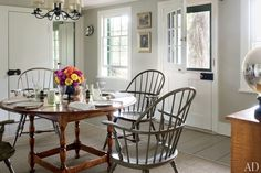 Vintage Windsor chairs surround a reproduction tavern-style table in the kitchen; the chandelier is by Period Lighting Fixtures, and a Beauvais sisal covers the painted original floorboards.