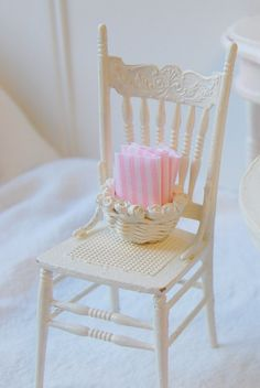 Miniature chair with a basket of pink linen