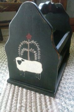 Wood magazine holder got at yard sale for $1, painted black,  draw and painted pictures on both ends.