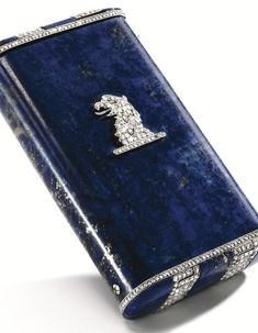 PLATINUM, DIAMOND, LAPIS LAZULI AND SAPPHIRE CIGARETTE CASE, JANESICH The case formed of one hollowed section of lapis lazuli, the top and bottom decorated with an openwork meander pattern and borders of numerous rose-cut diamonds, the front surmounted by a rose-cut diamond plaque of a griffin head, the sides accented by two small cabochon sapphires, signed Janesich, No. 16, 221; circa 1925.