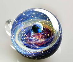 Glass artist Satoshi Tomizu sculpts small glass spheres that appear to contain entire solar systems and galaxies. Planets made of opals, flecks of real gold, and trails of colored glass seem to spin and loop like twists in the Milky Way. While photographed here in a macro view, the pieces are actu